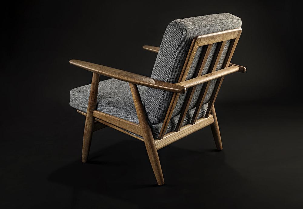 Ox&Bear Cigar Chair aus Holz vor schwarzem Hintergrund