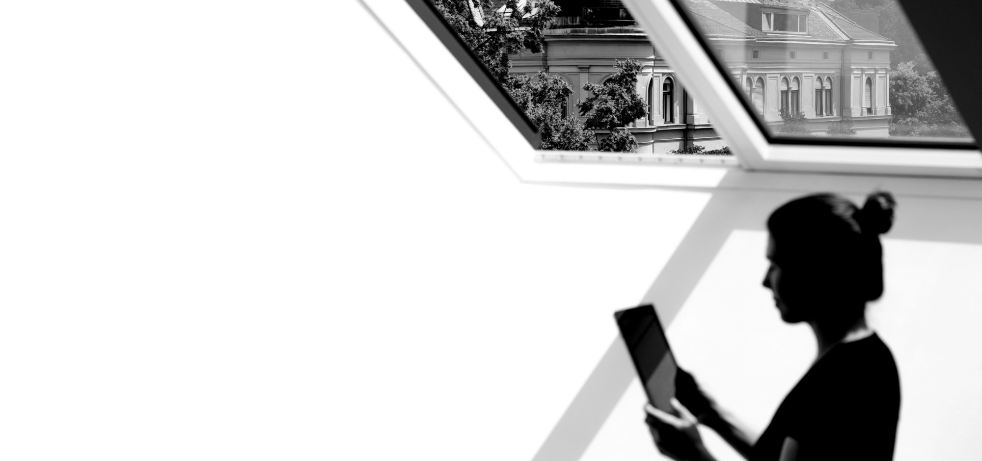 Frau am Tablet unter Dachfenster in Graz