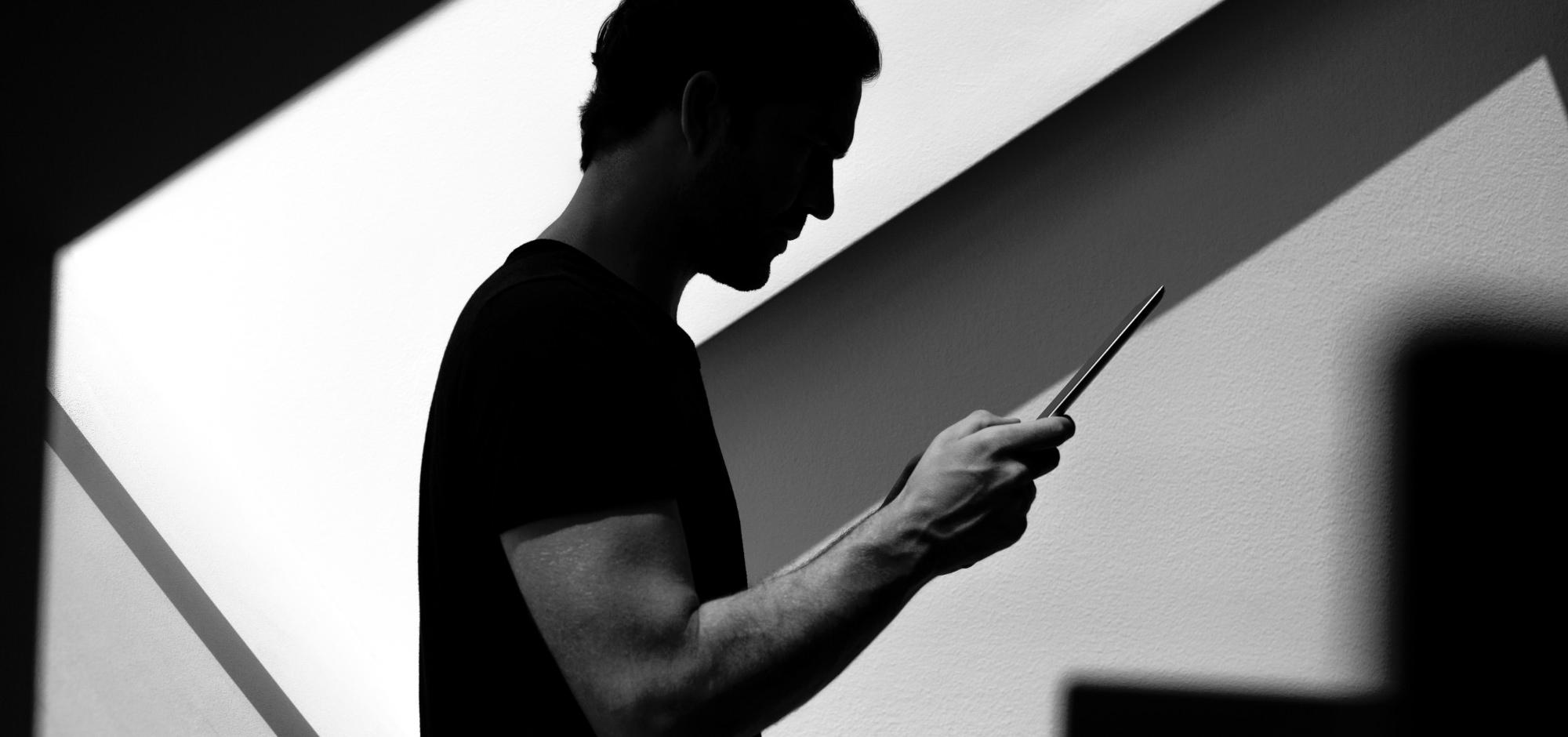 Kollege erledigt Kundenwünsche am Tablet unter Dachschräge in Schwarz-Weiß