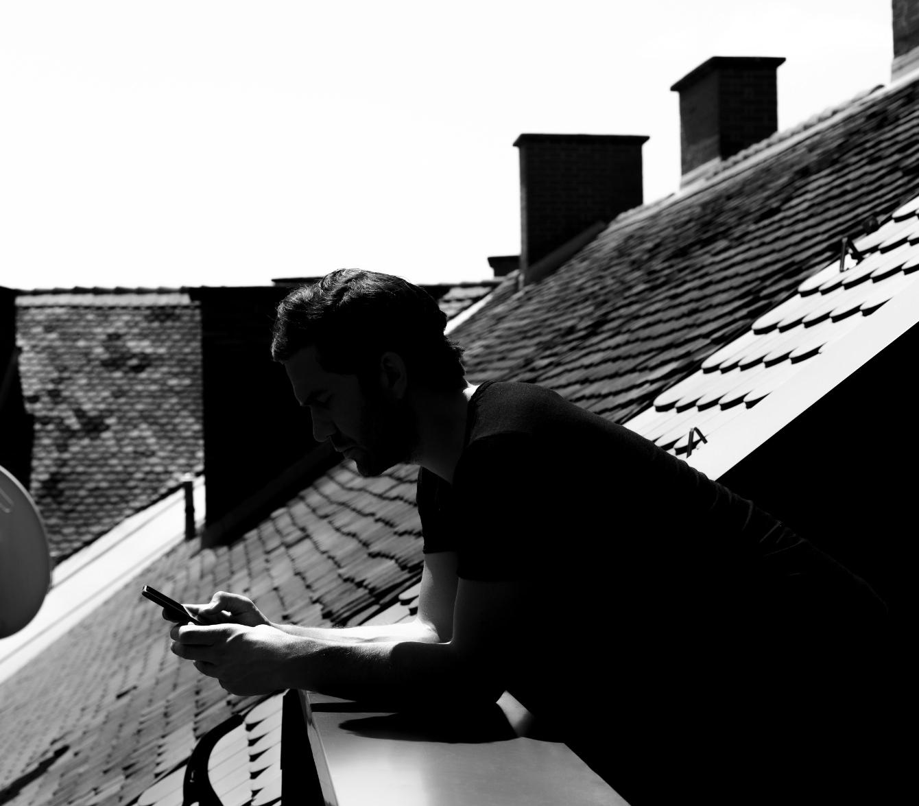 Conversory Mitarbeiter am Balkon lehnt am Geländer und tippt am Handy am Dach