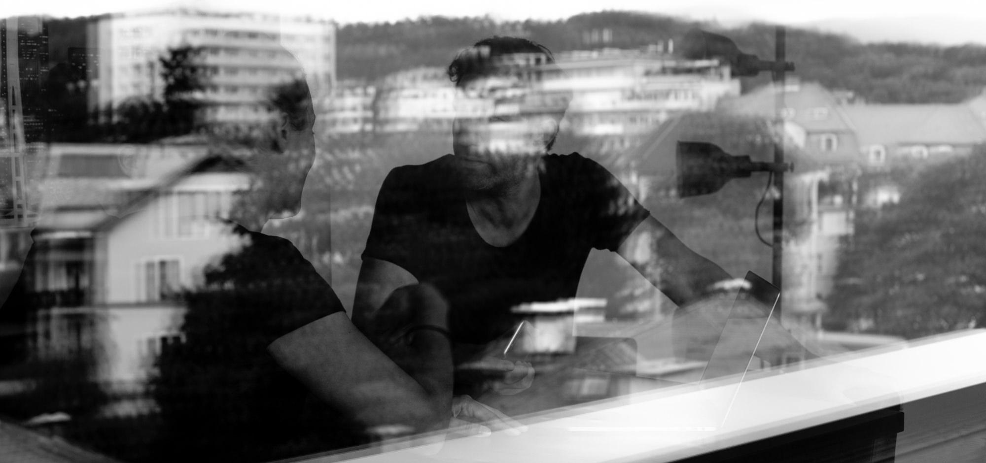 Conversory Mitarbeiter in interner Besprechung in der Agentur hinter Fenster am schreibtisch