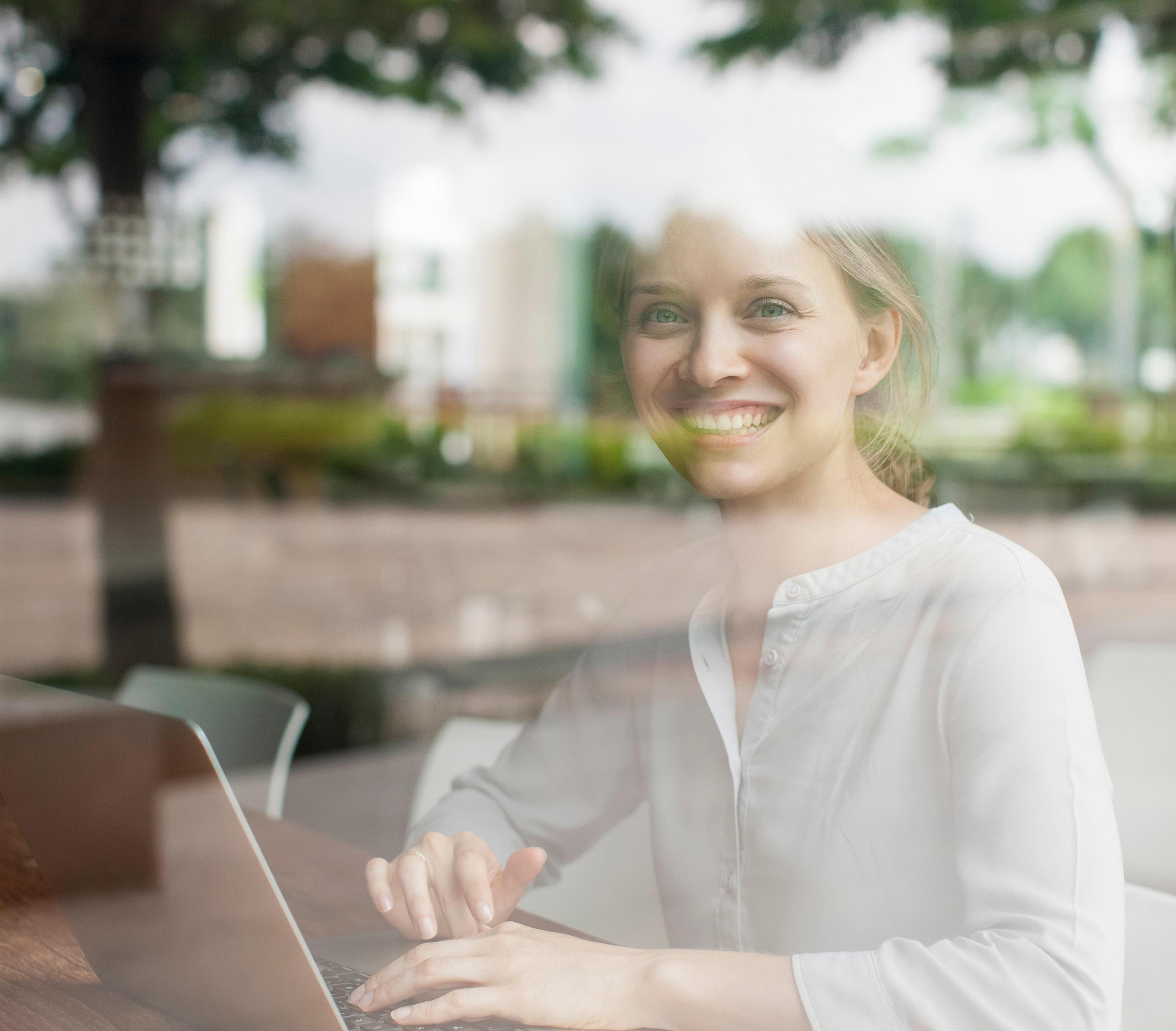 Frau sitzt mit Laptop am Tisch in einem Buerogebaeude