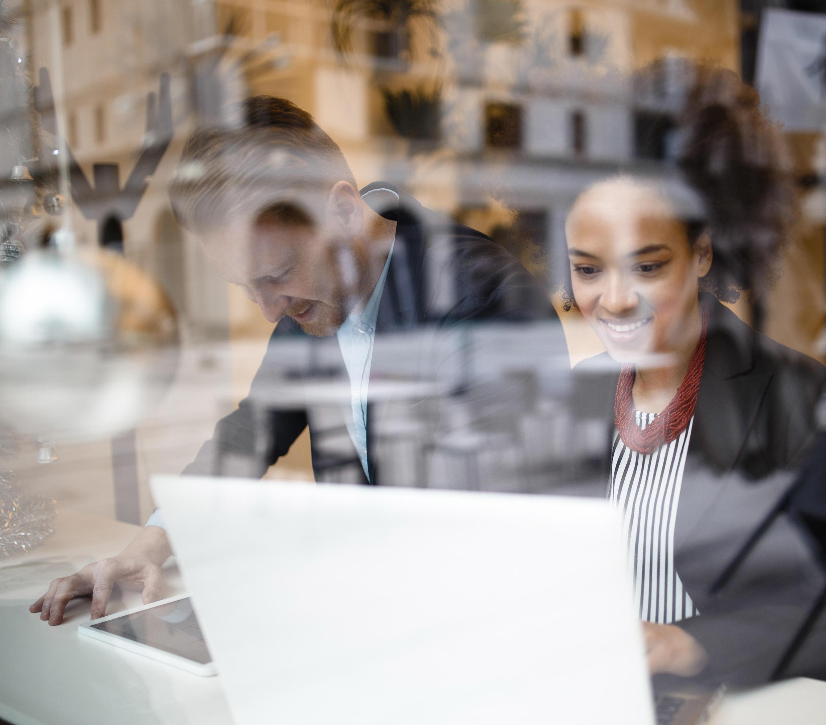 Mann und Frau stehen in Anzug vor Laptop mit dem digitalen Immobilienmanagement von Conversory