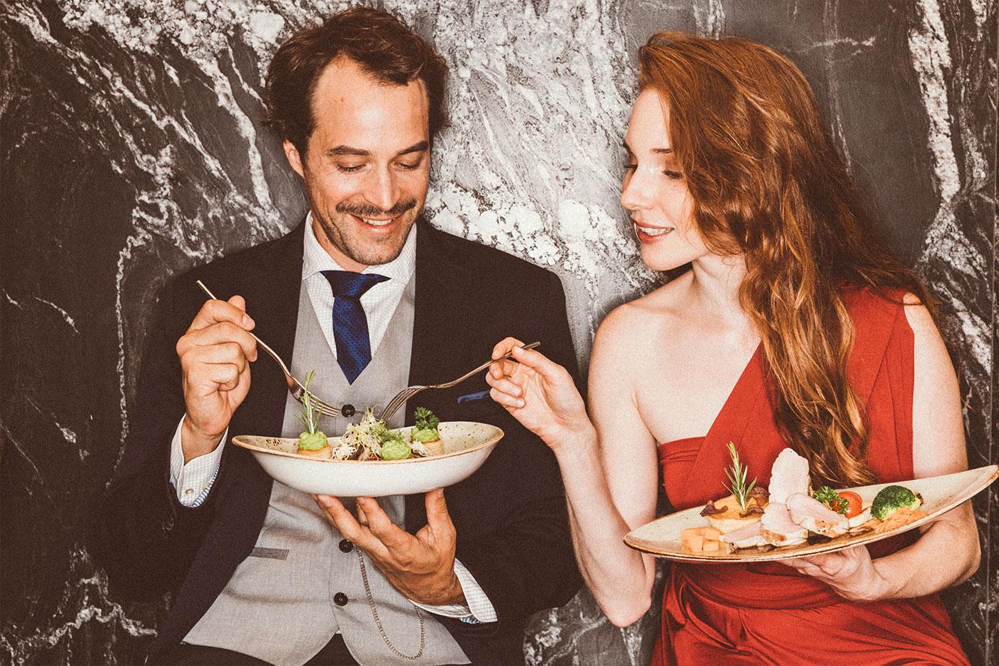 Pärchen in Abendkleidung mit Tellern probiert Essen vor Marmorwand