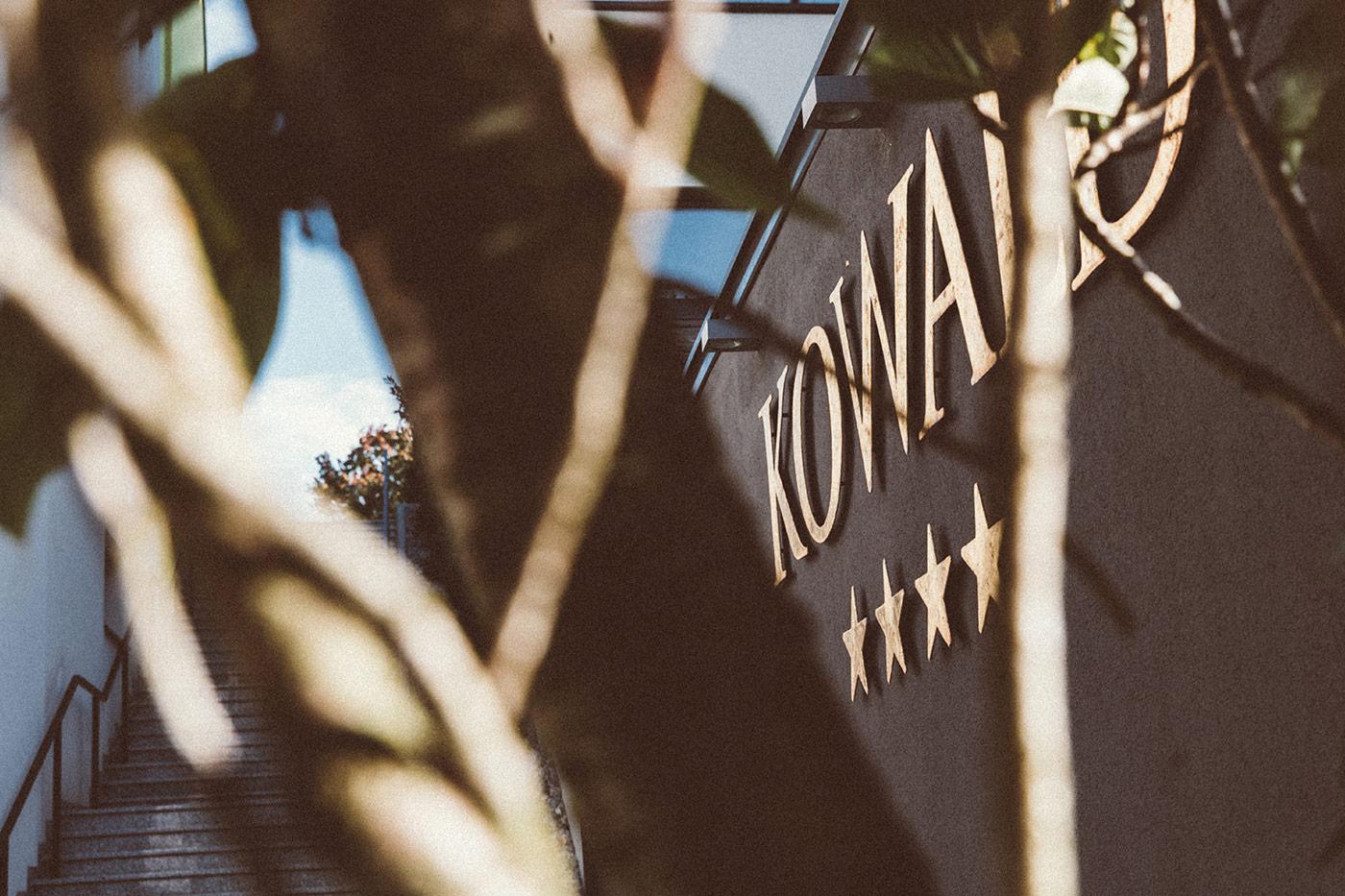 Hotel Kowald Schriftzug Fassade Feature mit Baum