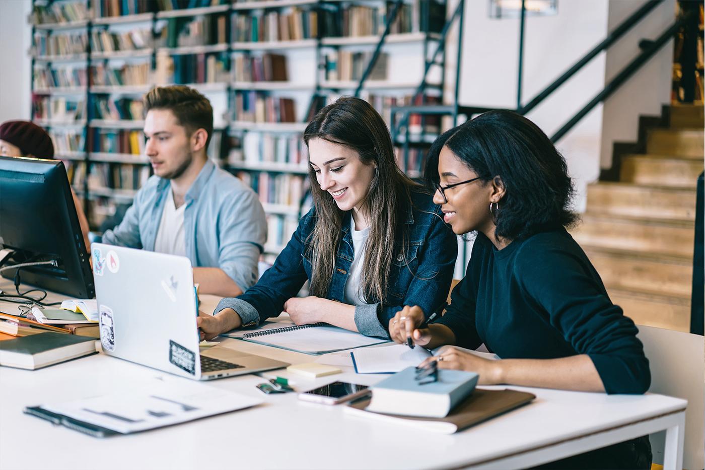 Studenten am Schreibtisch in Arbeitsraum mit Laptop und Unterlagen vor Bücherregal