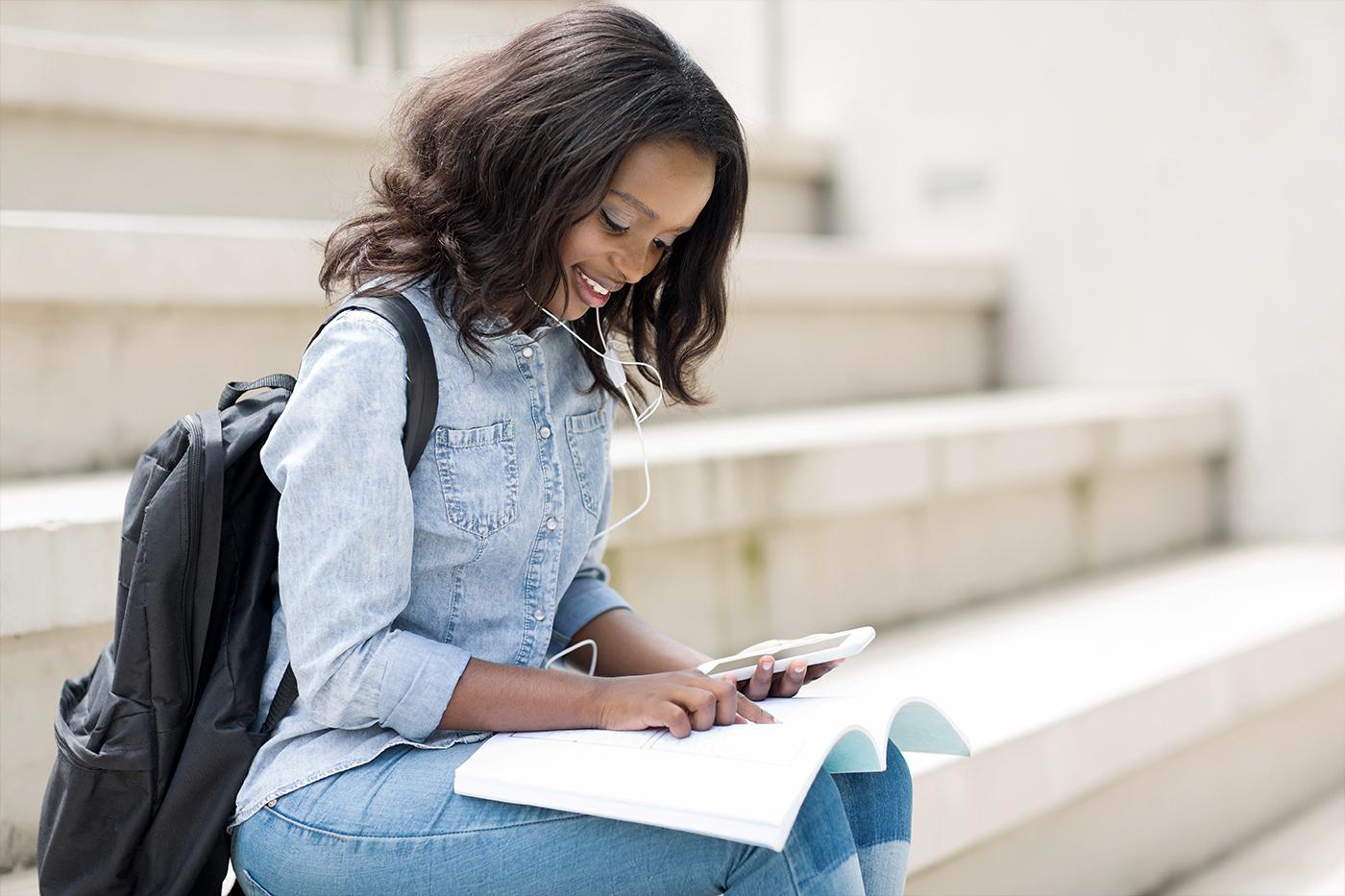 Studentin in Jeans mit Rucksack auf Treppe mit Handy, Kopfhörer und Buch im Freien