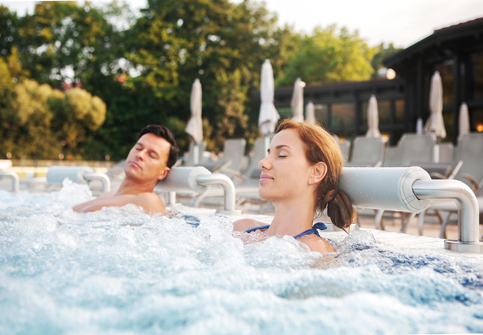 Heiltherme Bad Waltersdorf Paar genießt sprudelndes Thermalwasser beim Liegebereich