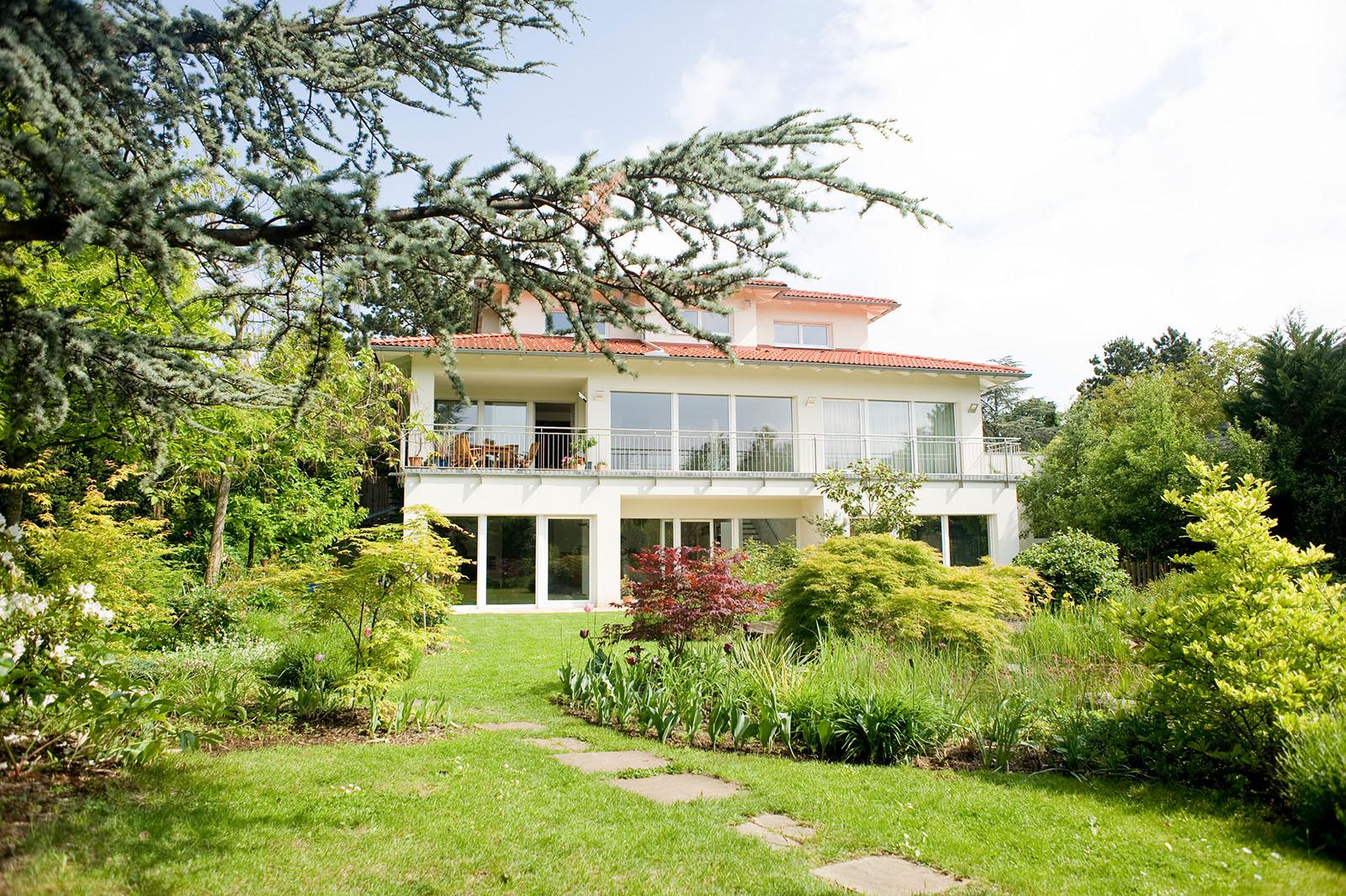 Wunschhaus Anwesen mit grosser Terrasse und Garten mit Bäumen im Sommer