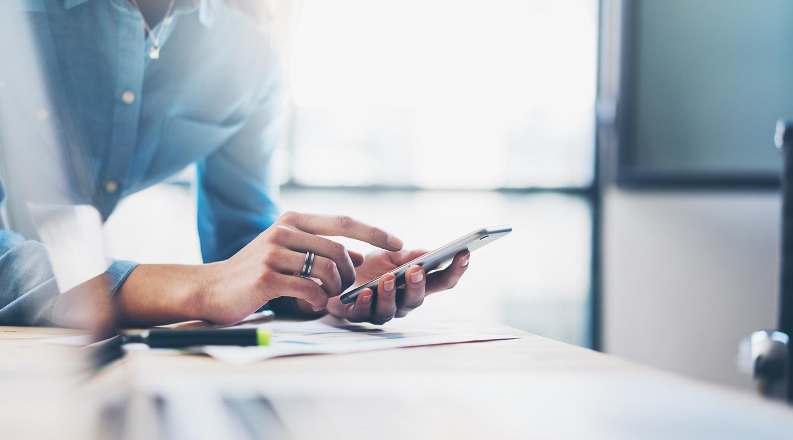 Frau mit blauer Bluse lehnt am Schreibtisch mit Smartphone Jolioo Tool