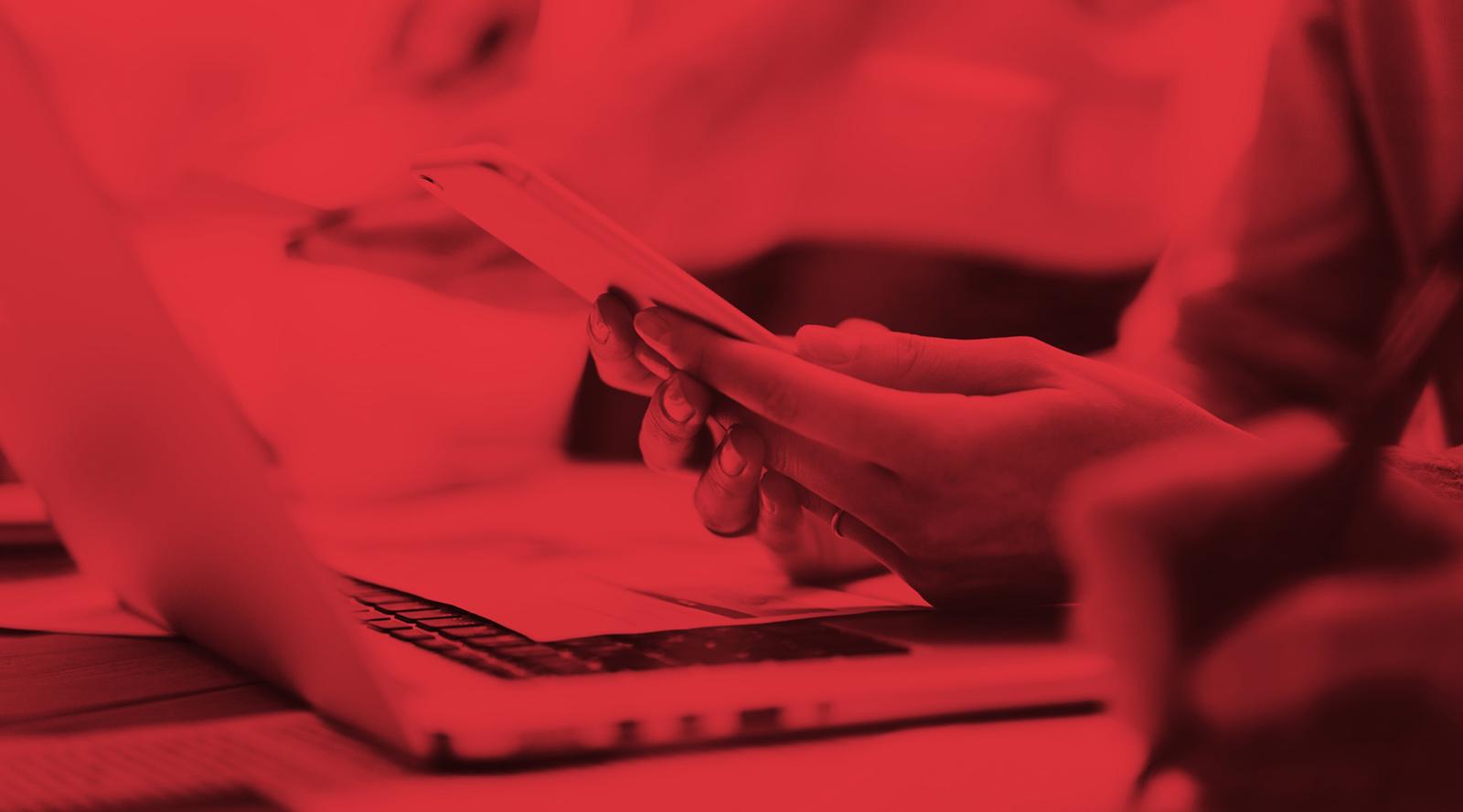 Frau mit Smartphone vor Laptop Detailansicht rot