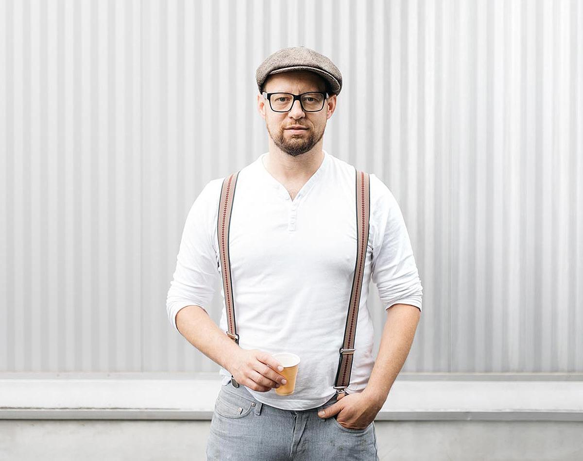 Fleischermeister Robert Buchberger mit Kappe Hosenträger vor gestreifter Wand