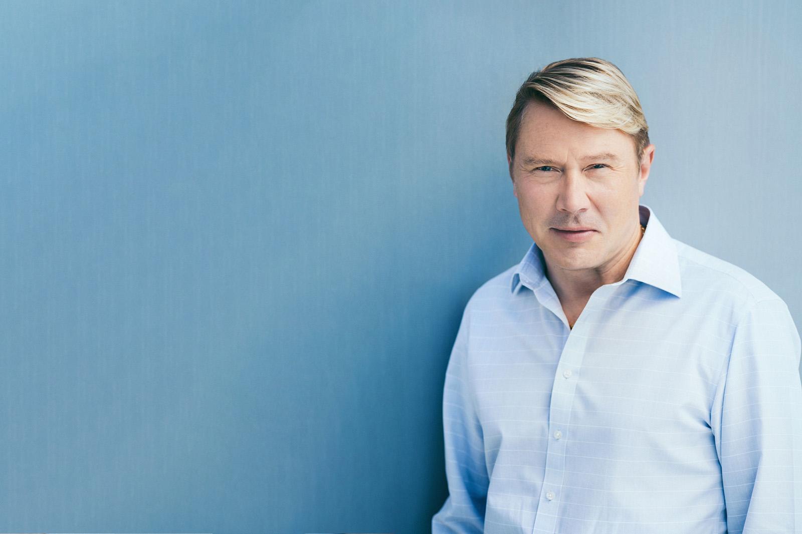 Neuroth Markenbotschafter Mika Häkkinen in blauem Hemd vor blauer Wand