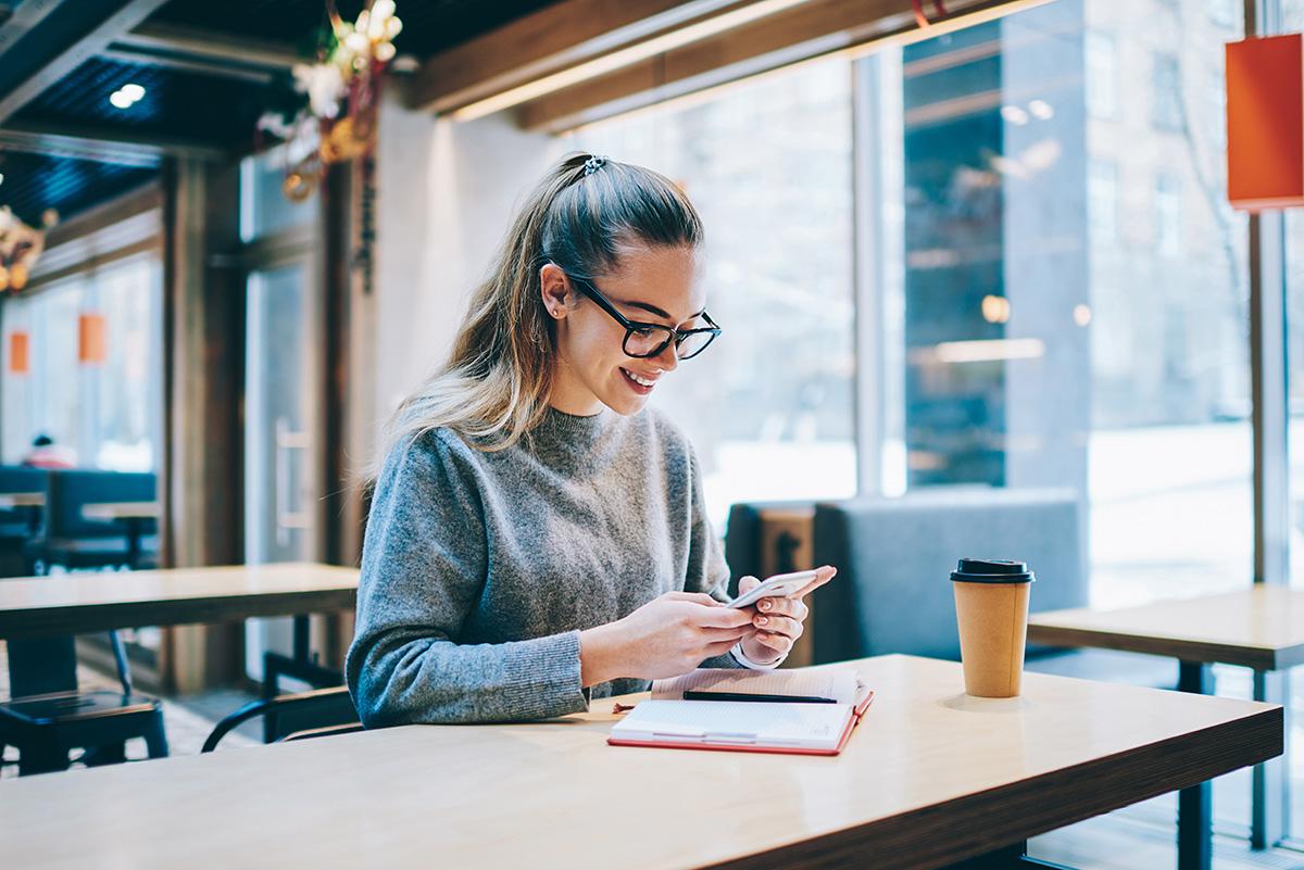 Studentin der Universität Graz mit Brille am Handy im Cafe