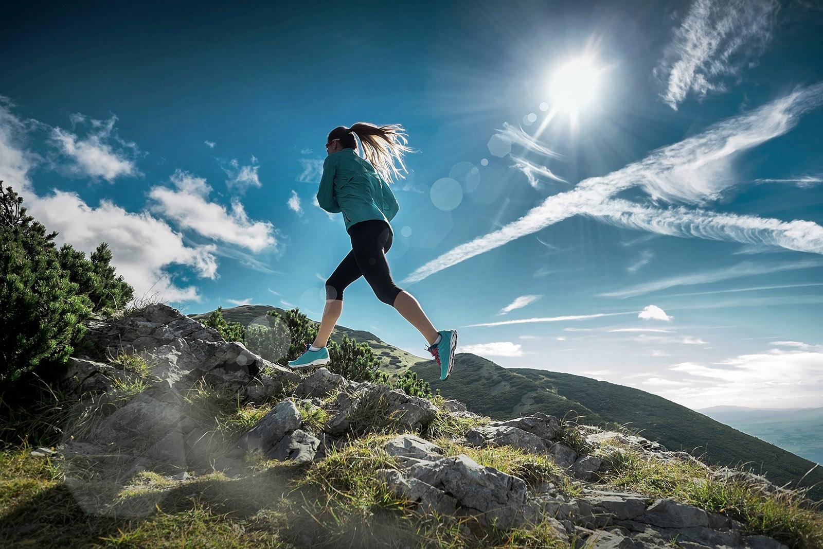 Sportliche Läuferin im Sprung am Berg mit Felsen und Sommerhimmel