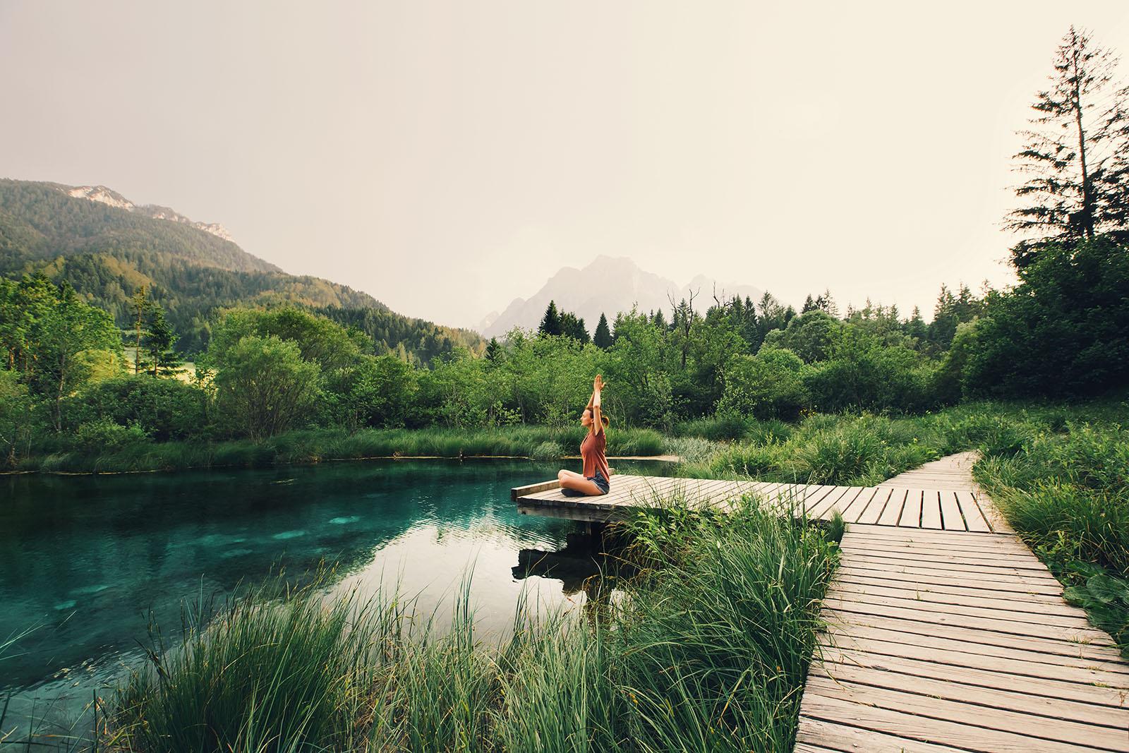 Frau macht Yoga am Steg an einem Bergsee mit Wald und Bergen im Hintergrund