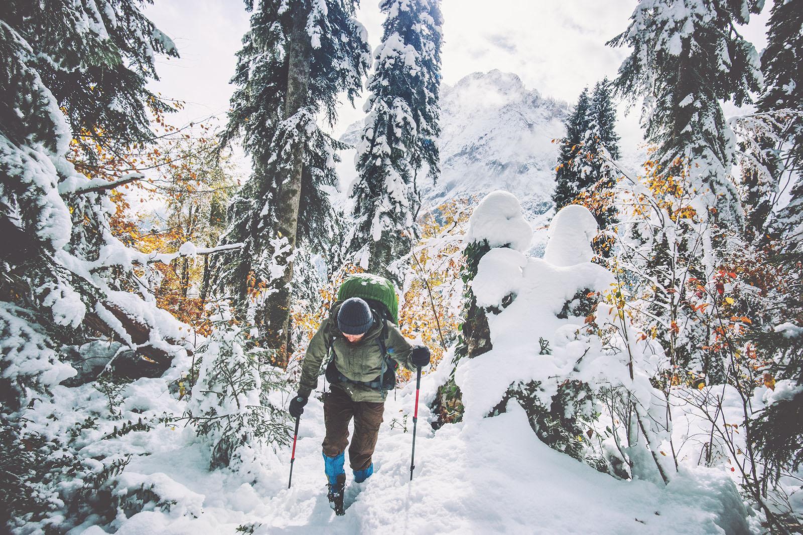 Bergwanderer im Wald auf verschneitem Berg mit Rucksack und Wanderstöcken