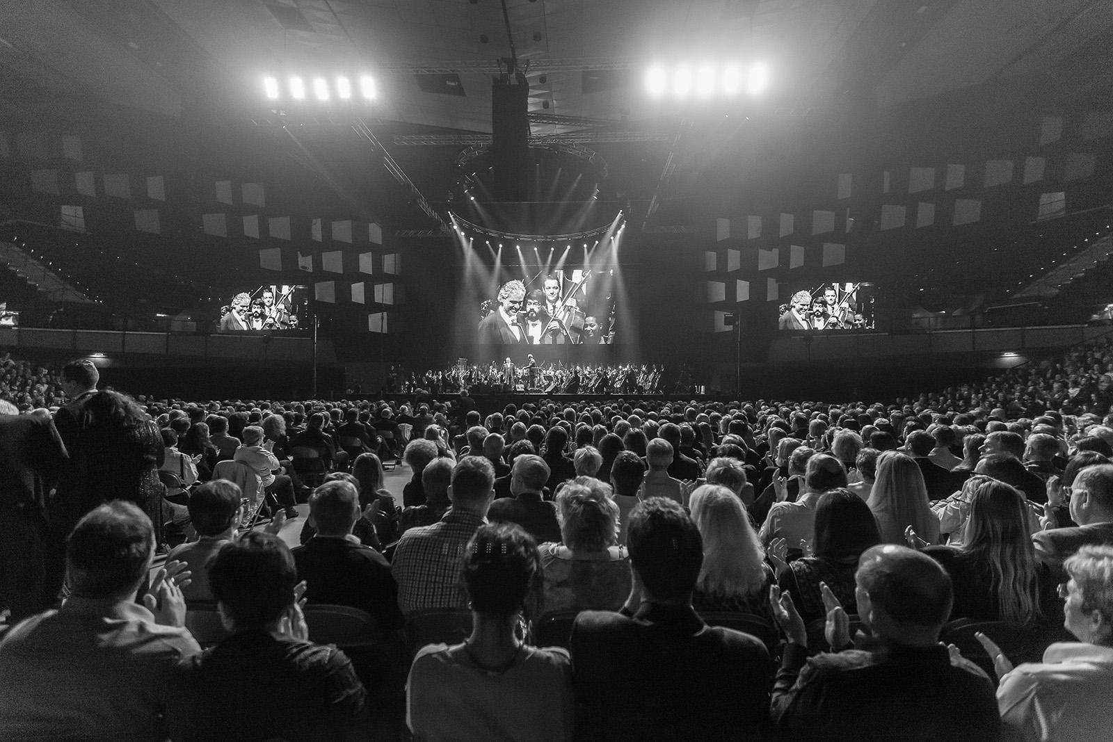 Andrea Bocelli auf der Bühne vor riesigem Publikum in schwarz weiss