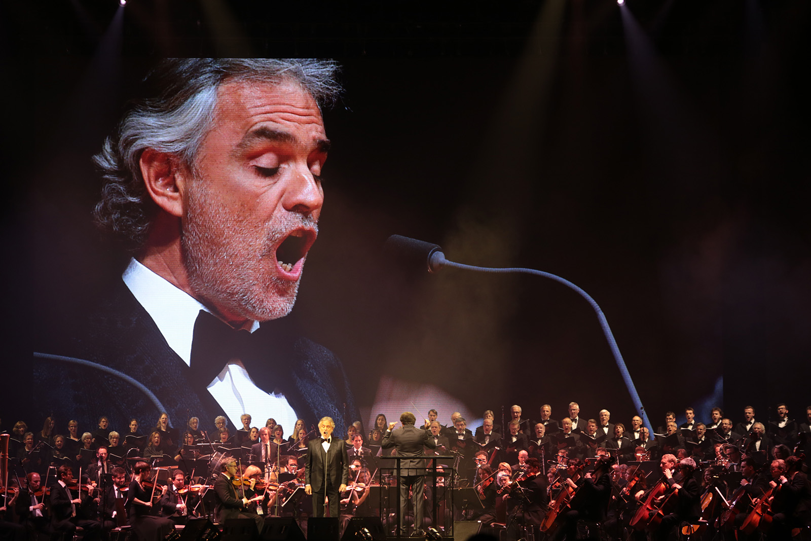 Andrea Bocelli auf Videowall mit Orchester vor dem Mikrofon