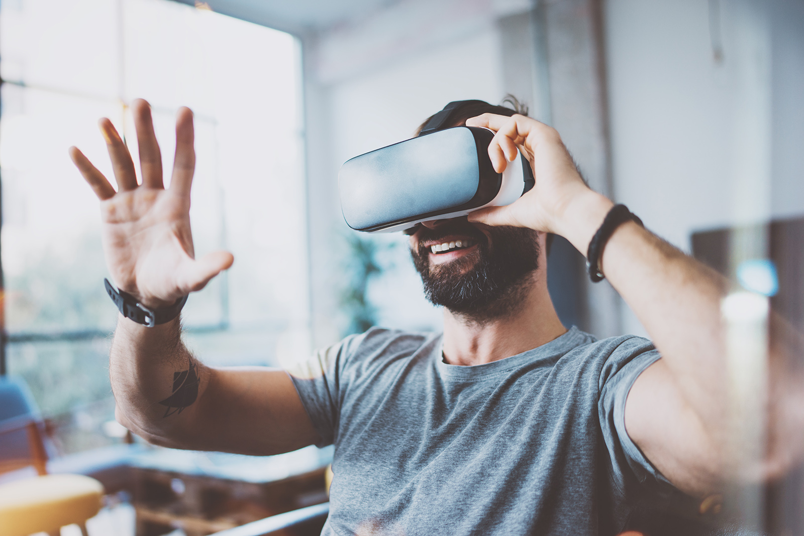 Mann testet 3D Brille im Sitzen zuhause im Wohnzimmer mit erhobener Hand