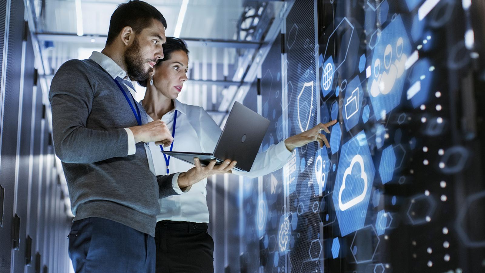 Analystin und Kollege vor dem digital Screen bei der Arbeit mit Laptop