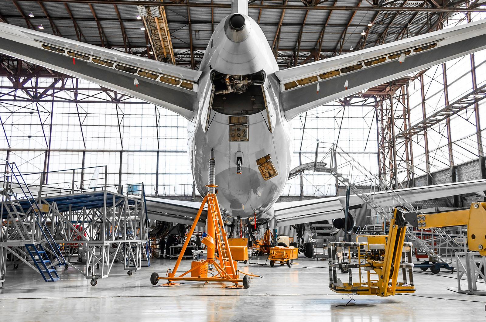 Flugzeug wird in einem Hangar gewartet Ansicht von hinten mit Kran