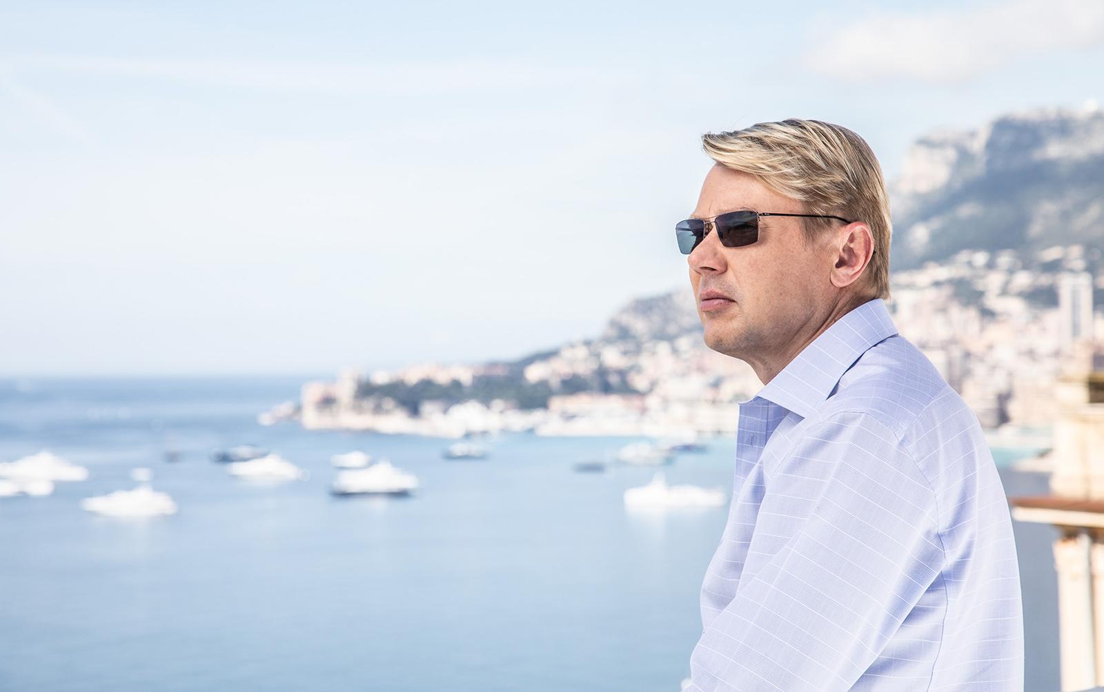 Mika Haekkinen mit Sonnenbrille und Hemd blickt auf Hafen