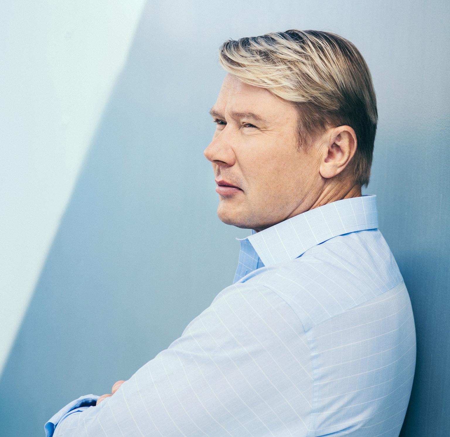 Portrait von Mika Haekkinen im Hemd vor einer Wand