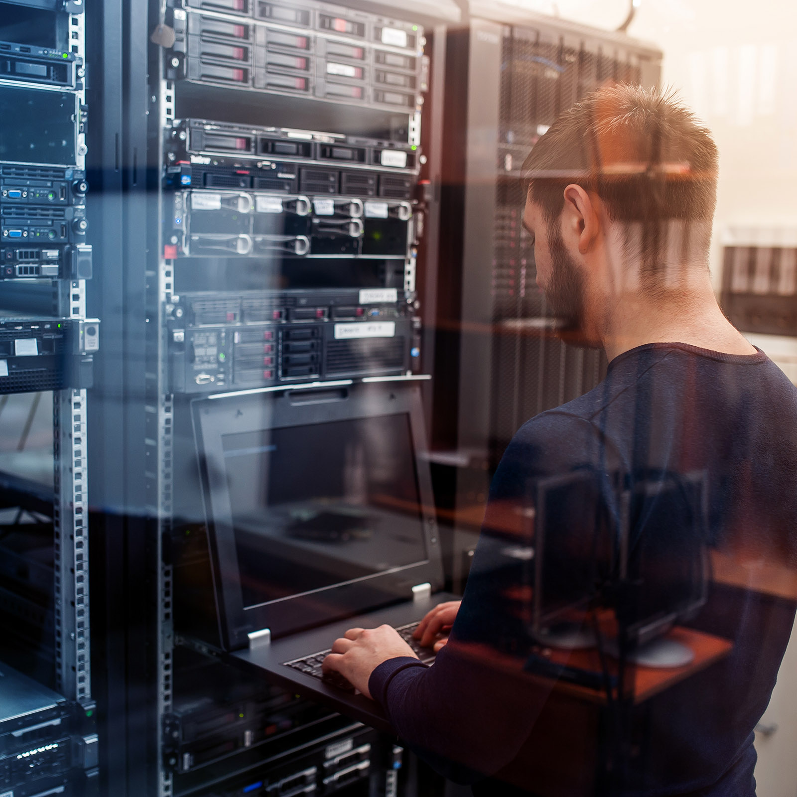 NTS Service-Techniker am Laptop im Serverraum bei der Arbeit