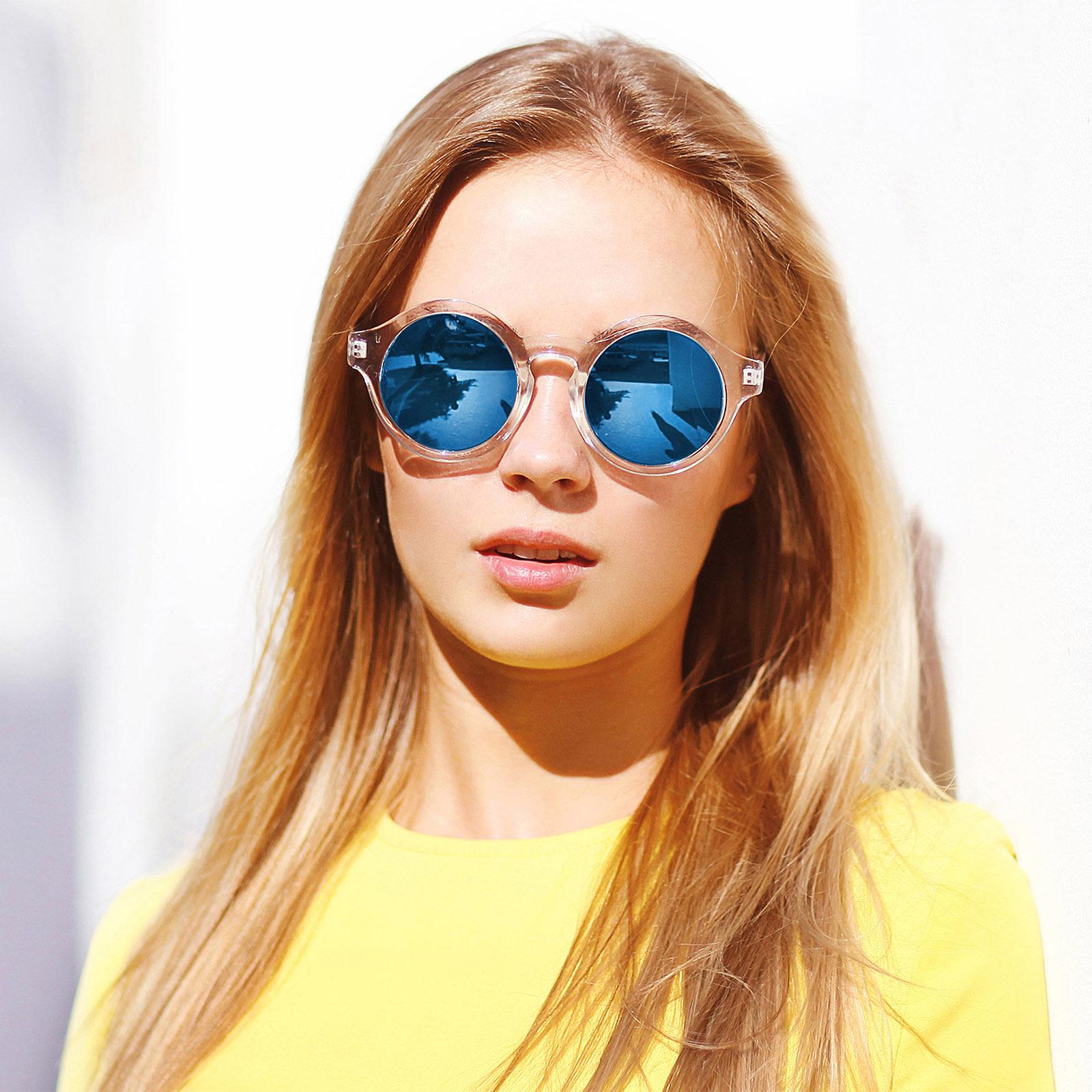 Rothaarige Frau mit Sonnenbrille und gelbem Shirt
