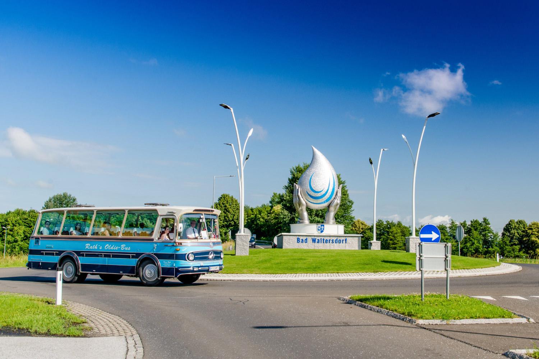 Blauer Bus biegt in der Tourismusregion Bad Waltersdorf in den Kreisverkehr
