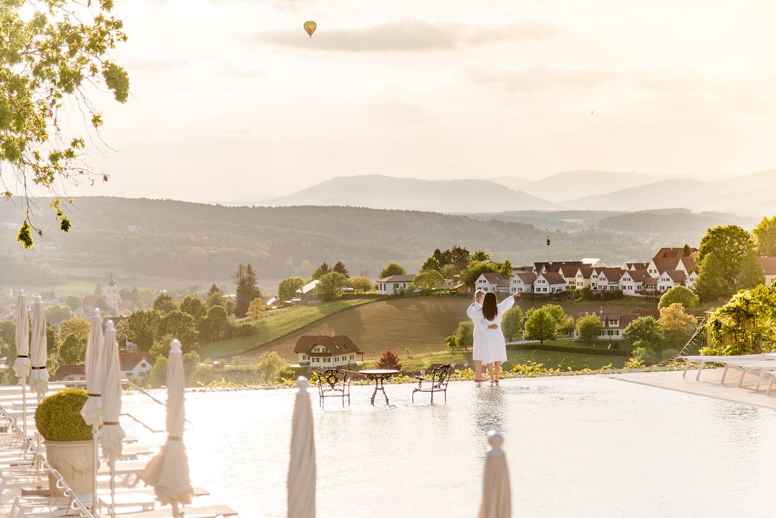 Frau steht in der Tourismusregion Bad Waltersdorf im Morgenmantel vor einem Pool und blickt auf die herrliche Landschaft