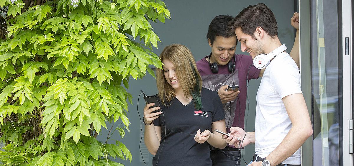 Studenten der TU Graz am Handy mit Pflanze und Glastüre