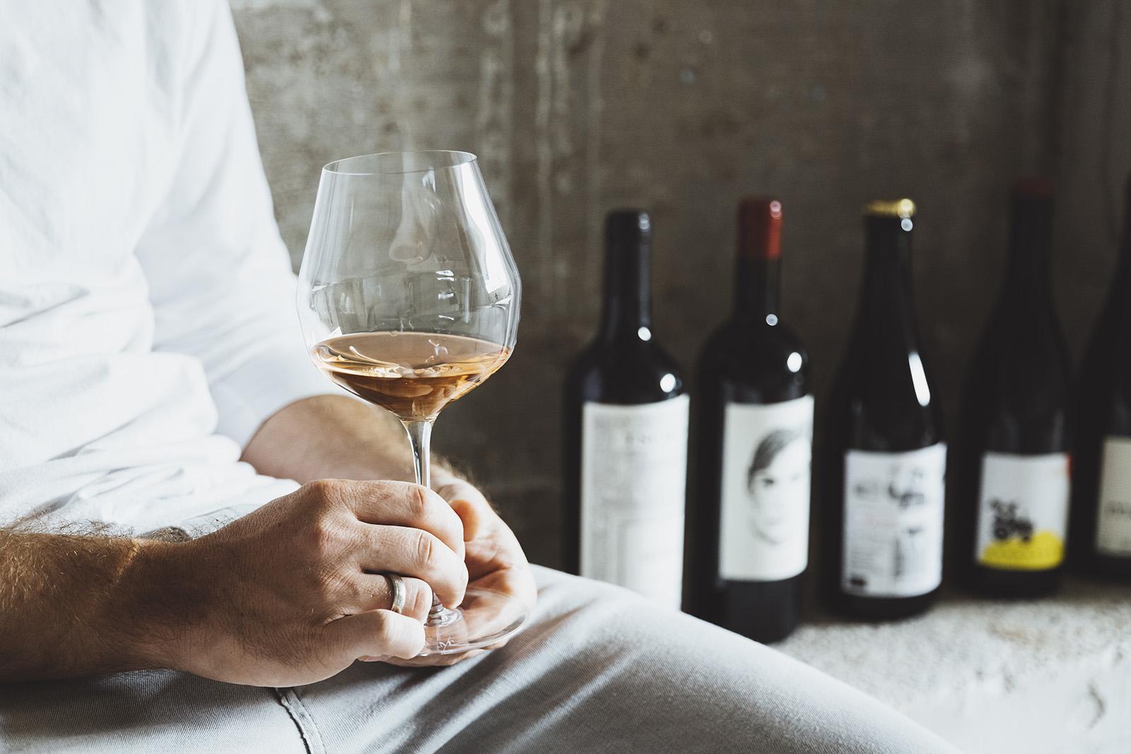 Manuel Veith sitzt mit Weinglas und Deko aus Weinflaschen im Concept-Store