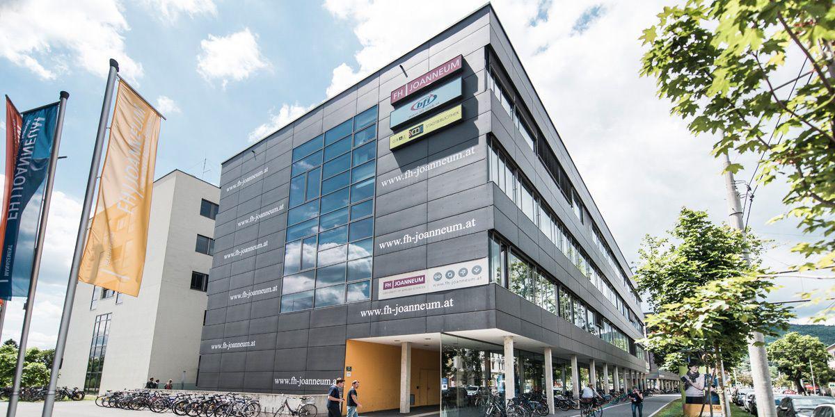 FH JOANNEUM Außenansicht der Gebäudefassade mit Logos, Fahnen und Baum
