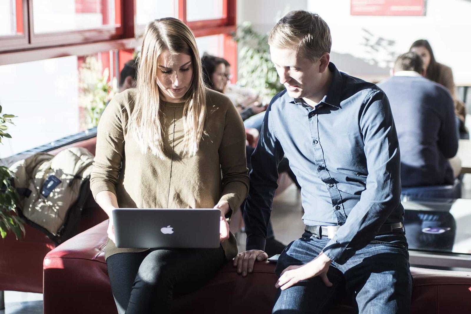 FH Studenten bei der Besprechung am Laptop auf roter Couchlehne sitzend