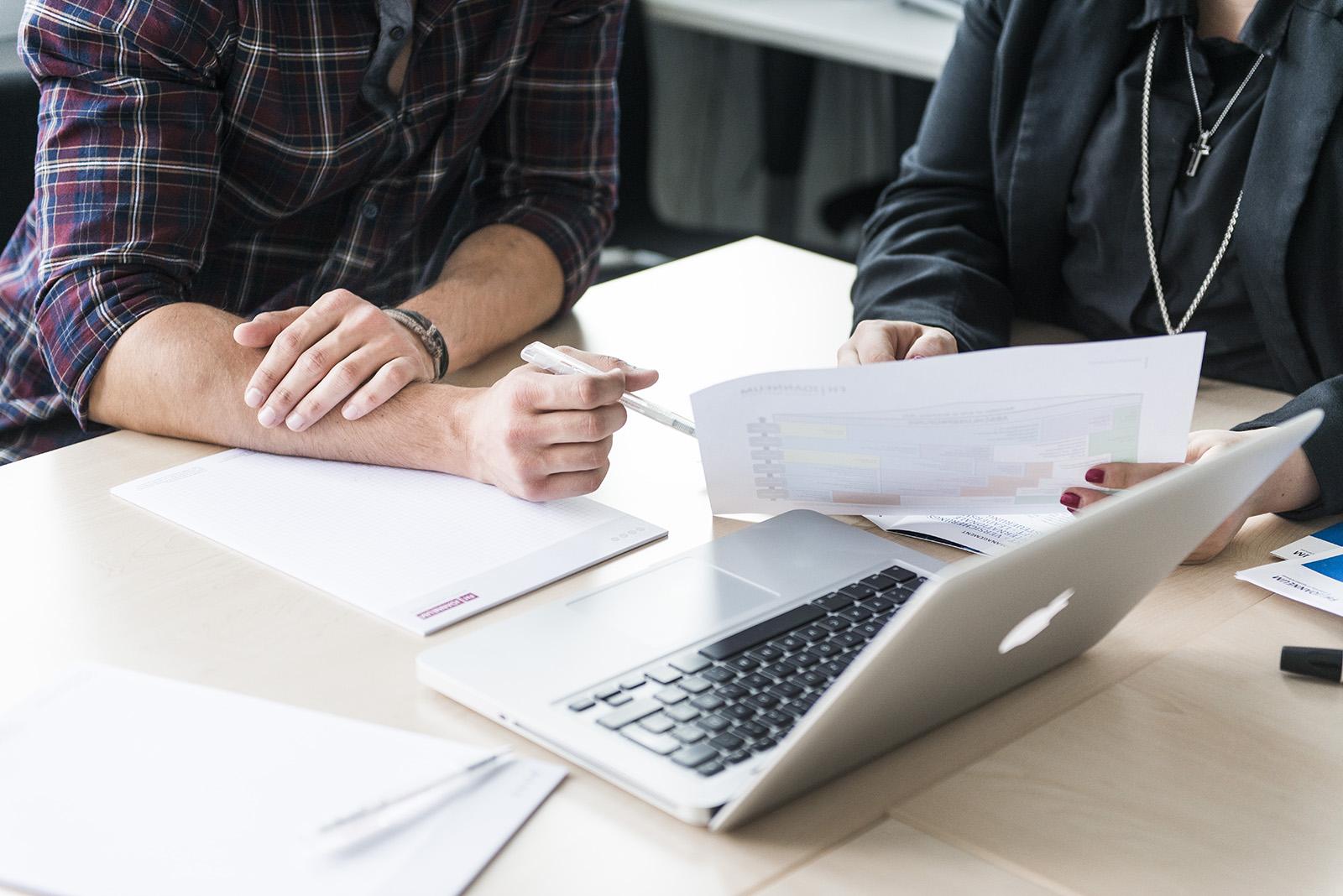 FH Studenten bei der Arbeit Detailansicht Schreibtisch mit Laptop