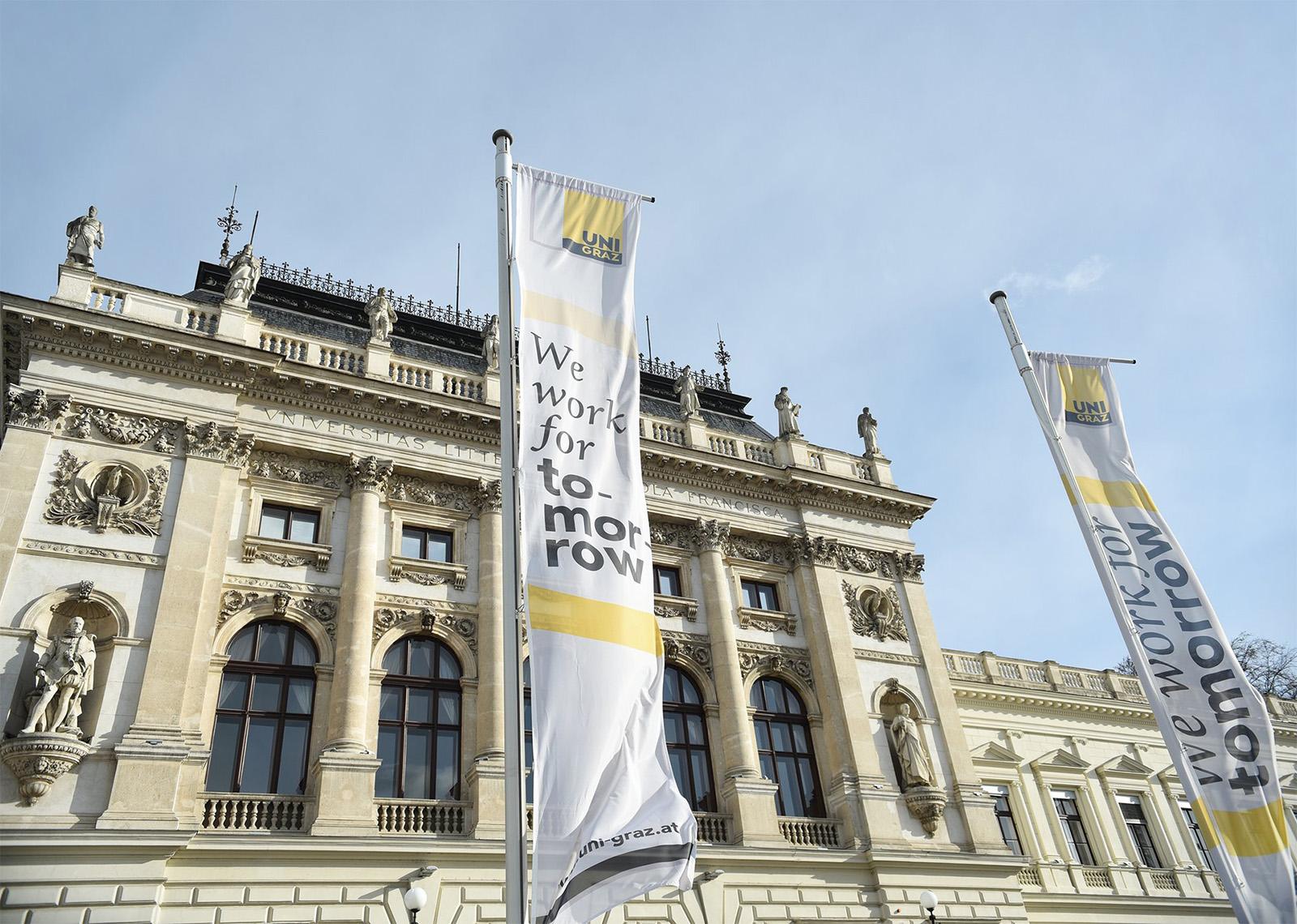 Uni Graz Außenansicht historische Fassade mit Fahnen