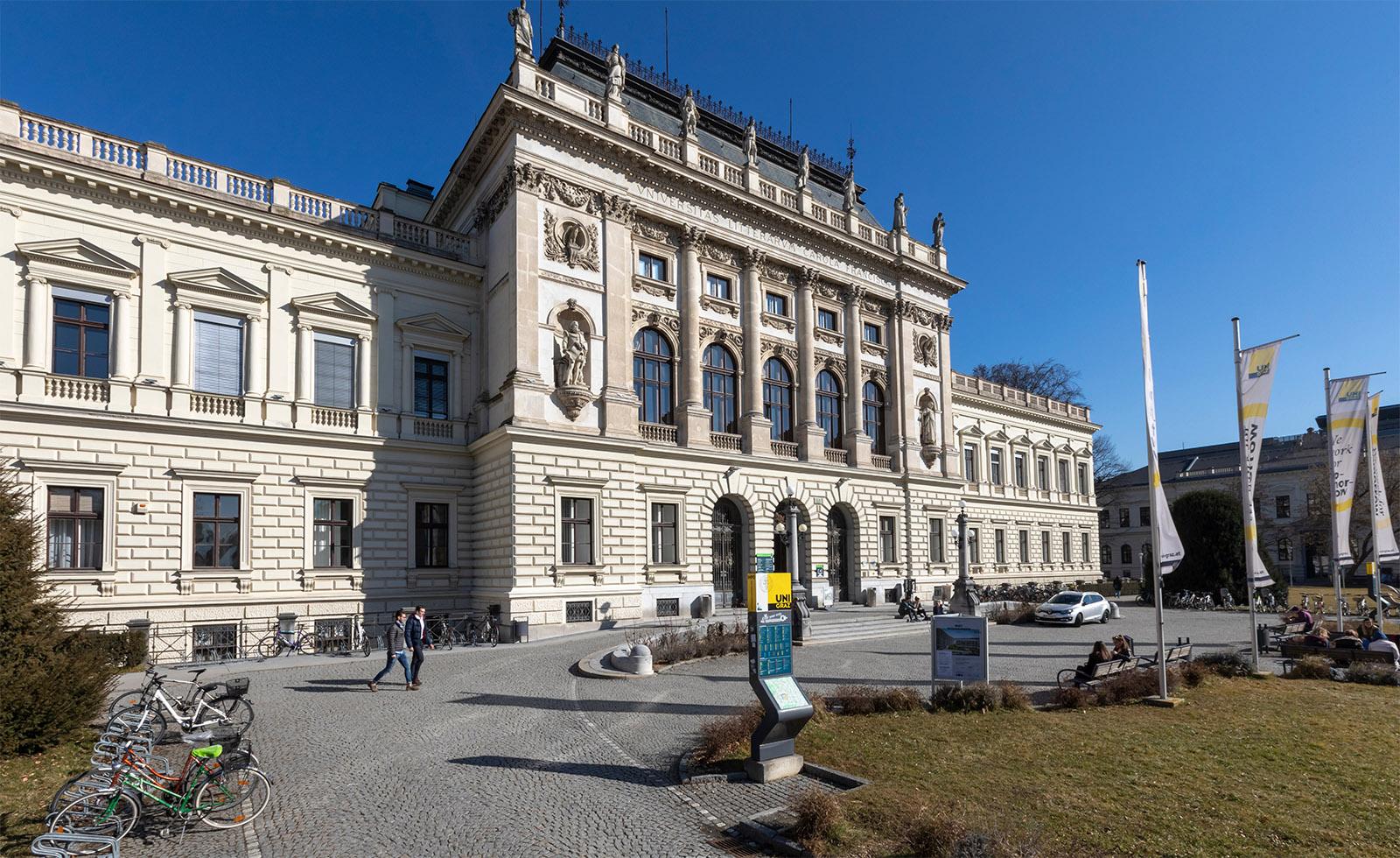 Uni Graz Außenansicht Hauptgebäude Front blauer Himmel und Wiese