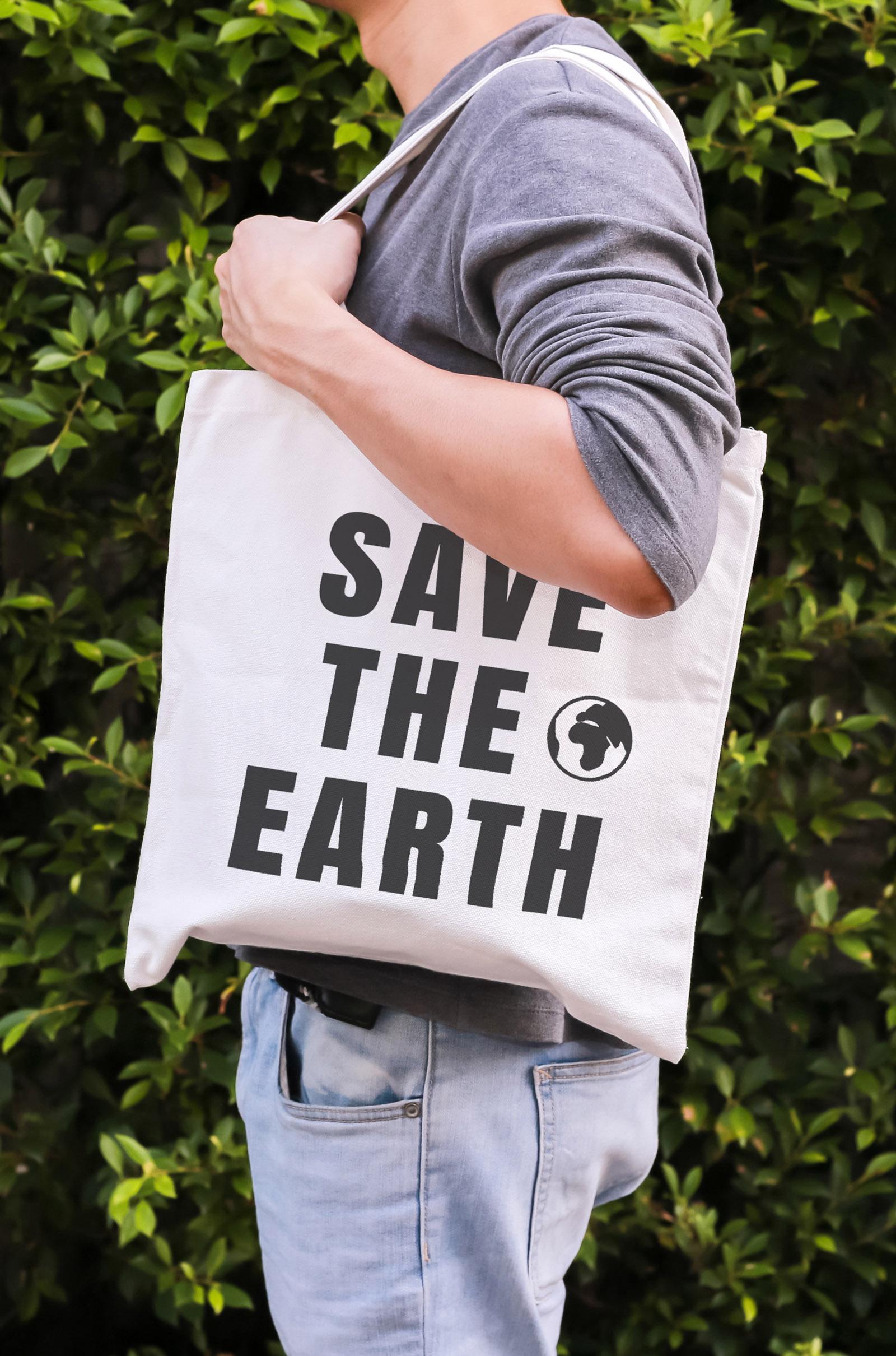 Klima Champ App-Mann mit Stoffsackerl mit save-the-earth Aufdruck steht vor belaubtem Busch