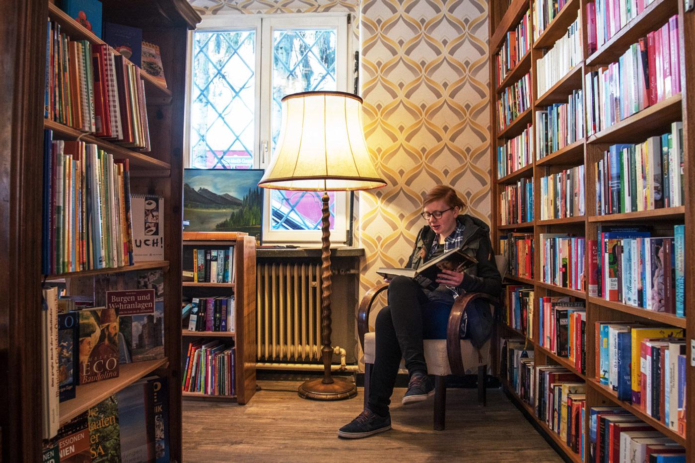 Lesende Kundin in einem Caritas Carla Shop mit Buch in der Bücherecke