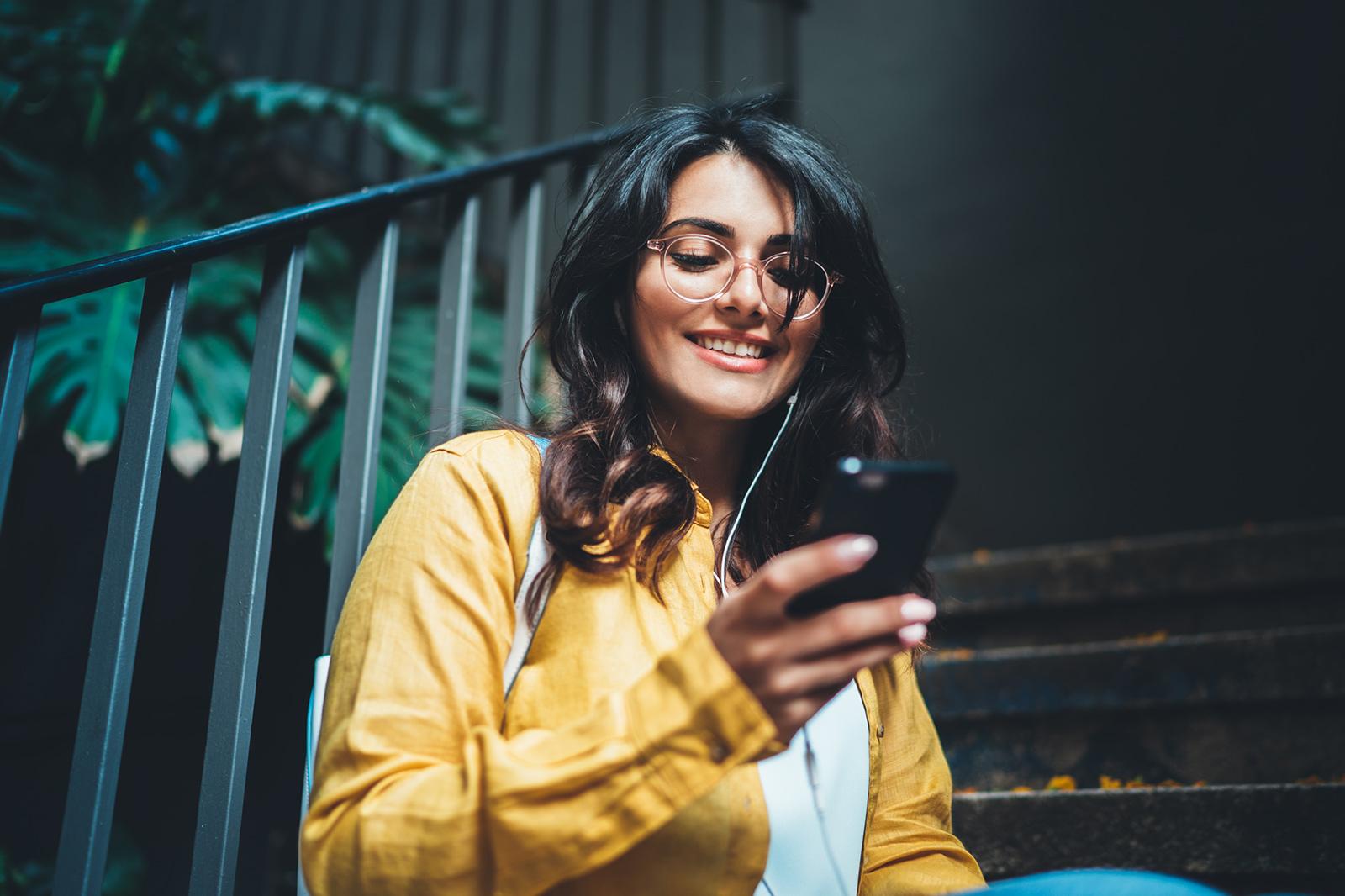 Studentin in gelber Jacke sitzt mit Handy und probiert das Online Bewerbungstool der Universität Graz von Conversory
