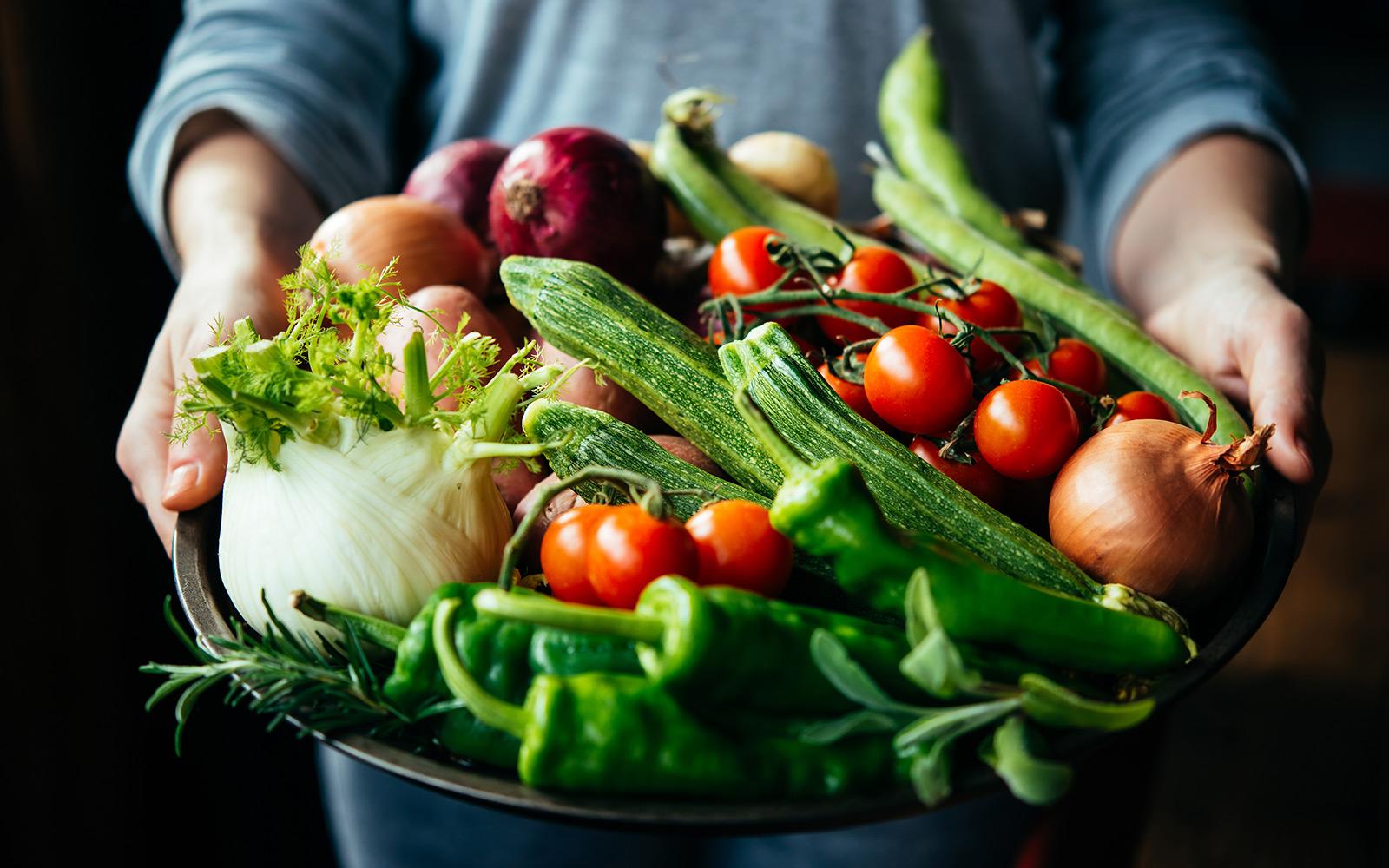 Frau hält Metallschüssel mit viel frischem Sommergemüse von Obsthaus