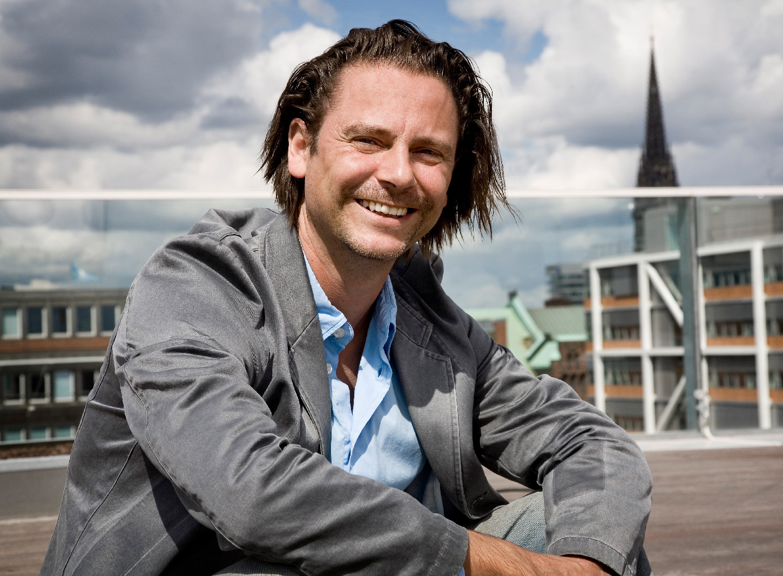 Mark Jenewein Teilnehmer der Biennale von LOVE architects lächelnd auf Dachterrasse in Graz Herz Jesu Kirche im Hintergrund