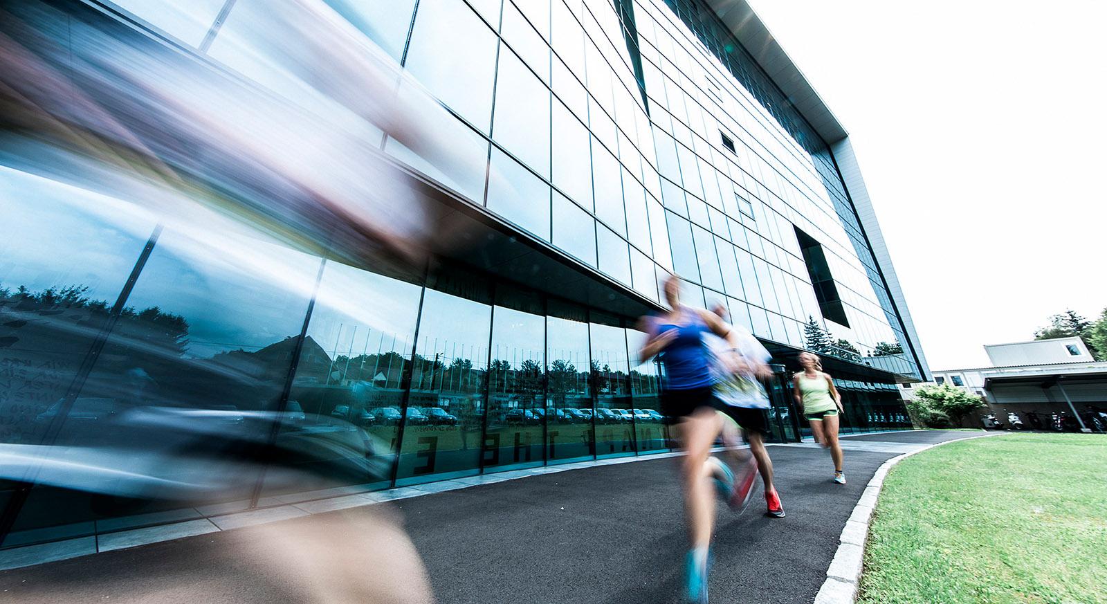 Glasfassade der Zentrale in Hart bei Graz mit drei sportlichen Läufern im Vordergrund © KNAPP AG