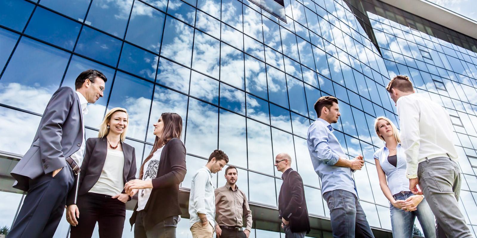 Mitarbeiter der HR Abteilung vor der Glasfassade der Firmenzentrale in Hart bei Graz beim Informationsaustausch in der Pause Firmengebäude mit Glasturm © KNAPP AG