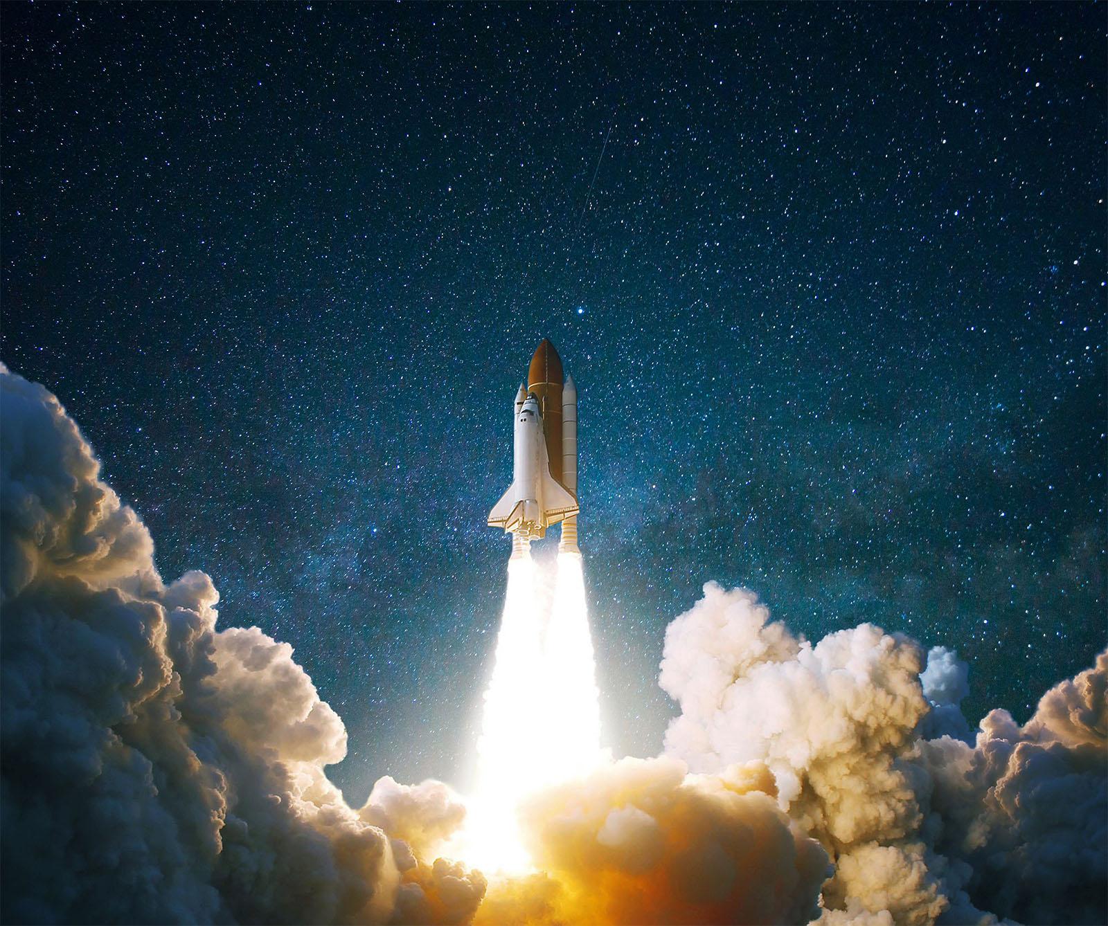 Spaceshuttle beim Start in den Sternenhimmel bei Nacht mit Rauchwolken
