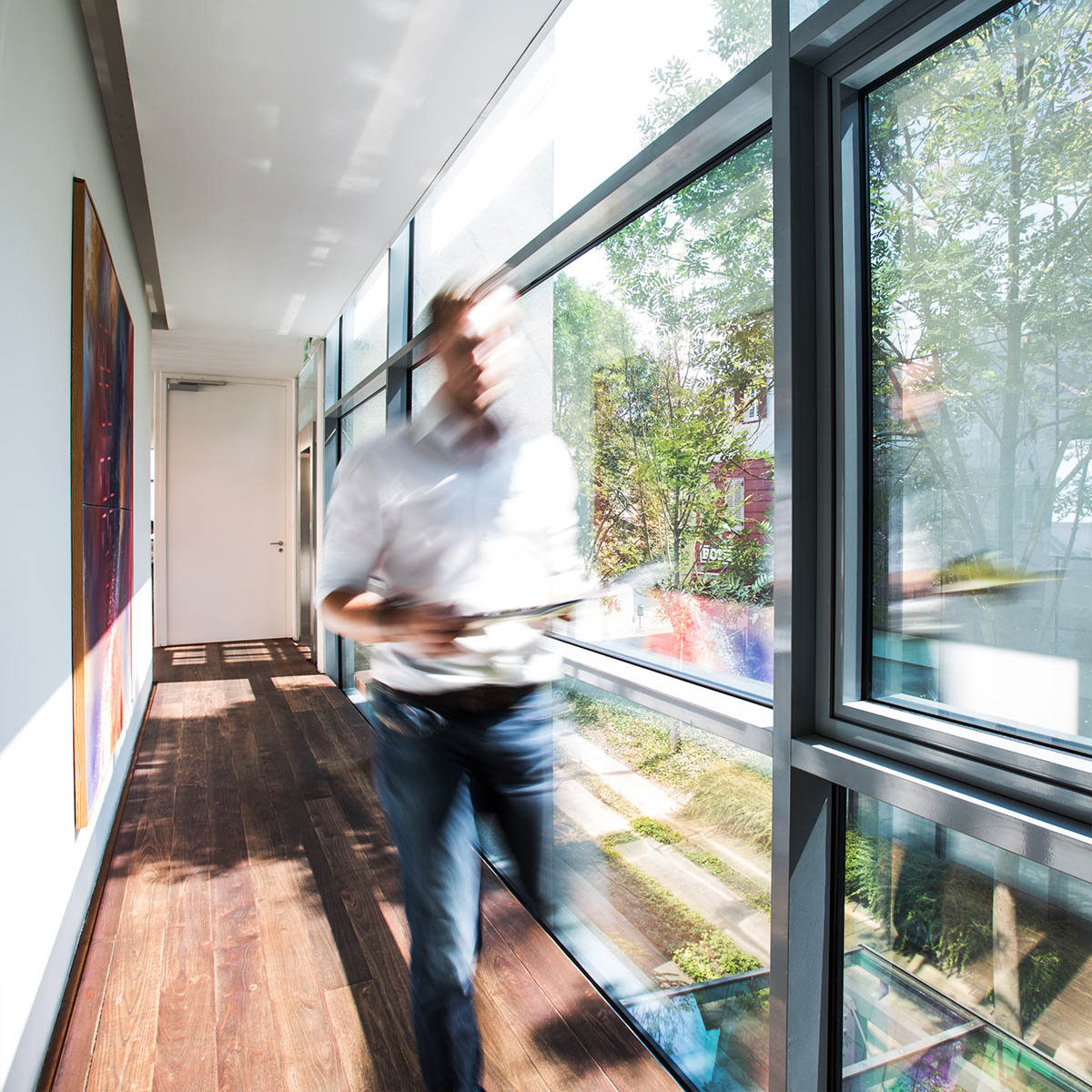 Mitarbeiter von Pilz + Rath geht durch den Glasgang im Gebäude der Steuerberatungskanzlei