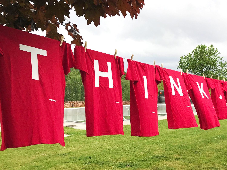 T-Shirts an einer Leine mit dem aufgedruckten Slogan der PMCC Consulting, Think - Create - Perform