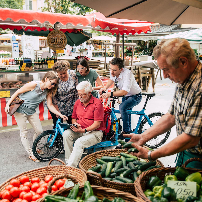 Gruppe von Leuten am Gemüsemarkt entdecken am Tablet den neuen digitalen Mitarbeiter Elmar von JOANNEUM RESEARCH